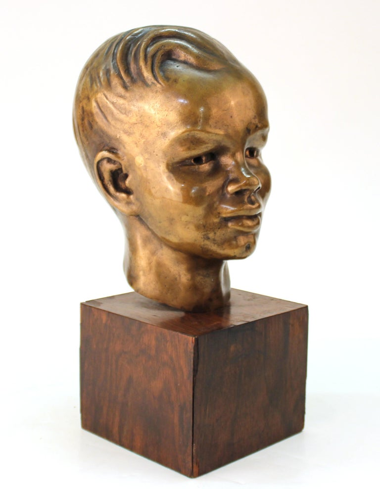 French Art Deco period sculpted bronze bust depicting the head of a young boy, atop a wooden base.
