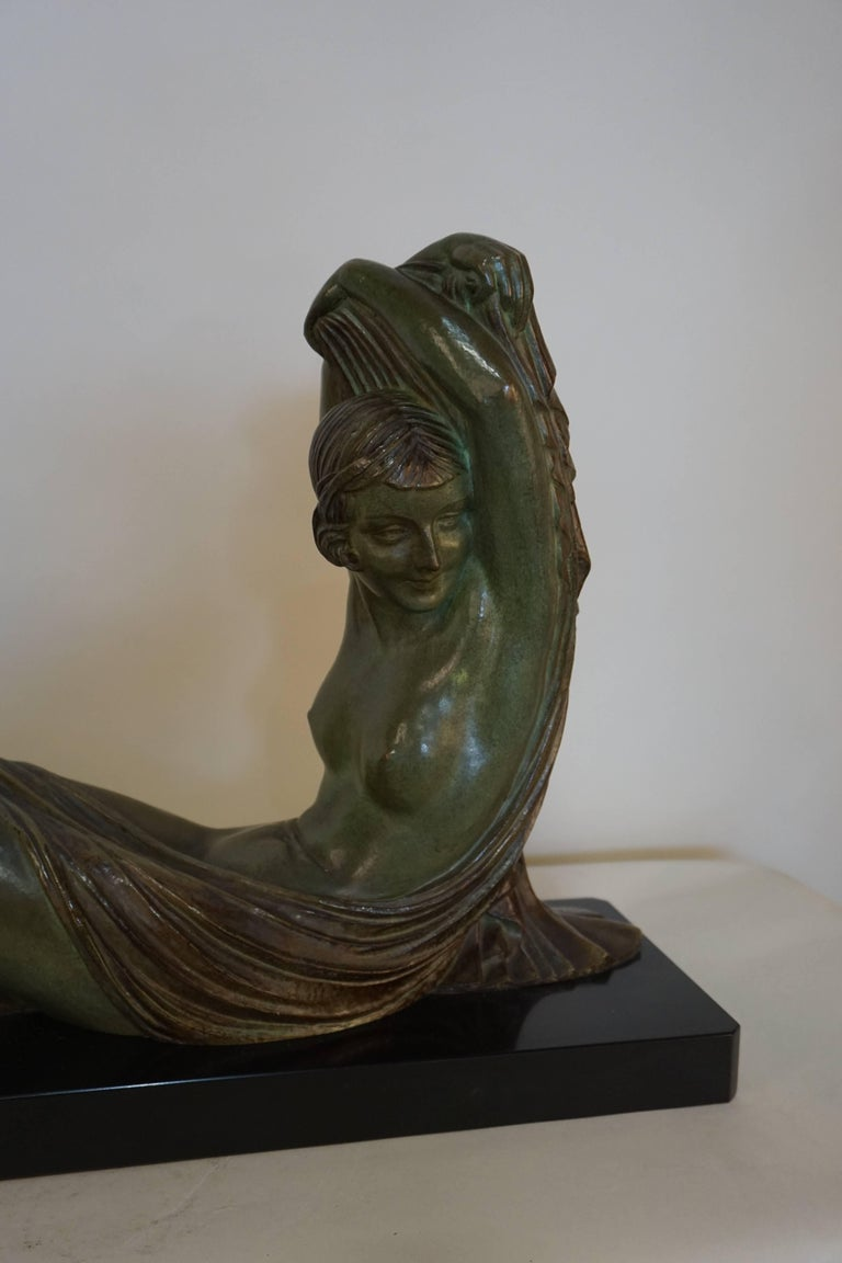 Patinated dark green or brown bronze over on black marble of seated nude woman by Demeter Chiparus and edited by Etling Paris Bronze.