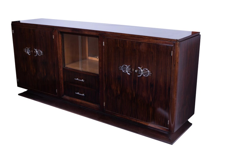Classic French Art Deco buffet or sideboard in solid Mahogany veneered in Macassar Ebony. The piece has a niche in the center with glass doors and mirror back. Chromed hardware.  Made in France, circa 1925.