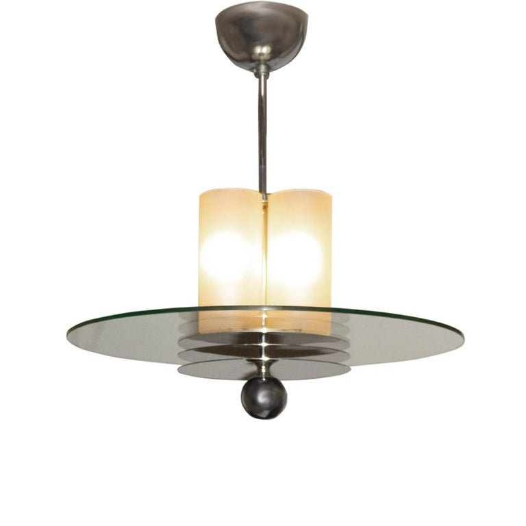 An Art Deco period pendant light fixture. Features a center round glass piece suspended from a burnished nickel stem with matching ceiling canopy. Complemented by a lighted frosted glass shade and a burnished nickel ball. France, circa
