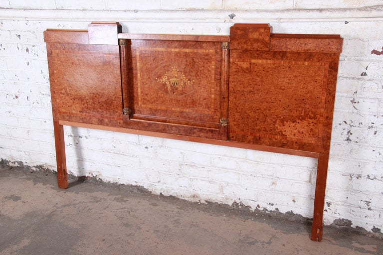 An exceptional French Art Deco burled olive wood king size headboard  France, circa 1930s  Burled olive wood + inlaid mahogany + brass  Measures: 78