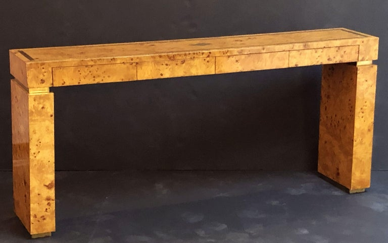 A fine French Art Deco style console table, of burled wood with brass accents, attributed to a design by Jean Claude Mahey. Featuring stylish architectural or sculptural design - this rectangular console table was designed with four fitted short