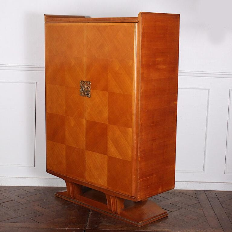 A French Art Deco two door cabinet with cherry-veneered chequer-board parquetry front and gilt bronze figural key plate, the whole raised on simple geometric legs above a plinth base with metal trim. Adjustable shelves to the interior. C. 1930 –