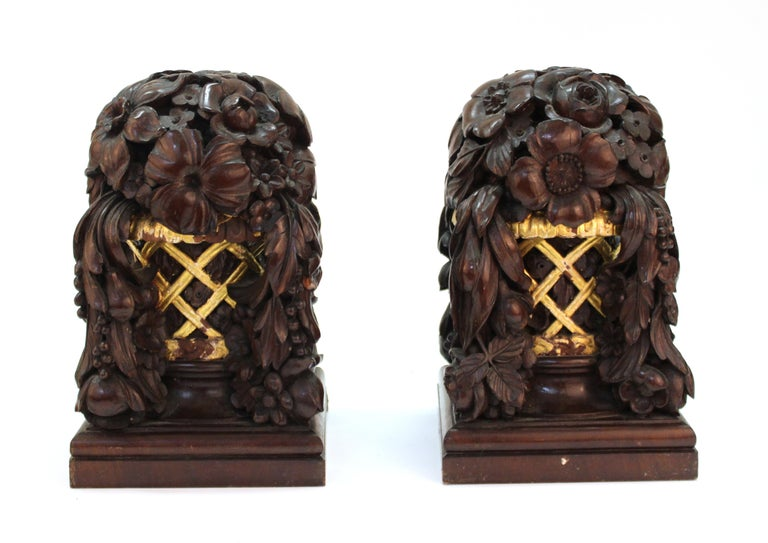 French Art Deco carved and partially gilt wood decorative floral baskets with cascading fruit garlands attributed to French designers Louis Sue and Andre Mare. The pair was likely designed as decorative finials or architectural elements for an Art