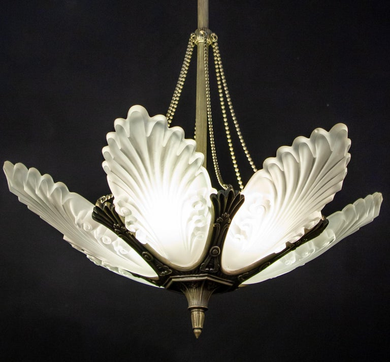 Elegant French Art Deco chandelier with six grand clear frosted molded shades with a silvered metal frame.  We can Rewire to U.S. standards which accommodate six E 14 light bulbs . Custom drop; we can shorten the rod on request.