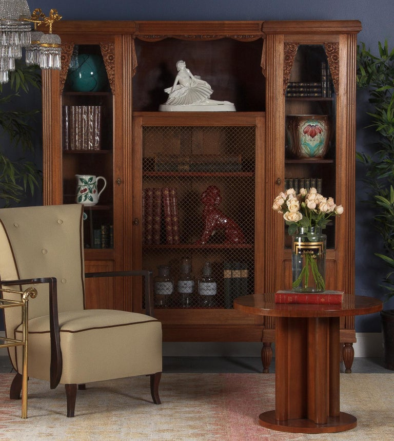 A stunning 3-door French bookcase from the Art Deco period in cherrywood. The sides feature paneled door with original glass and floral motifs at tops. Inside are 4 adjustable shelves 13.75