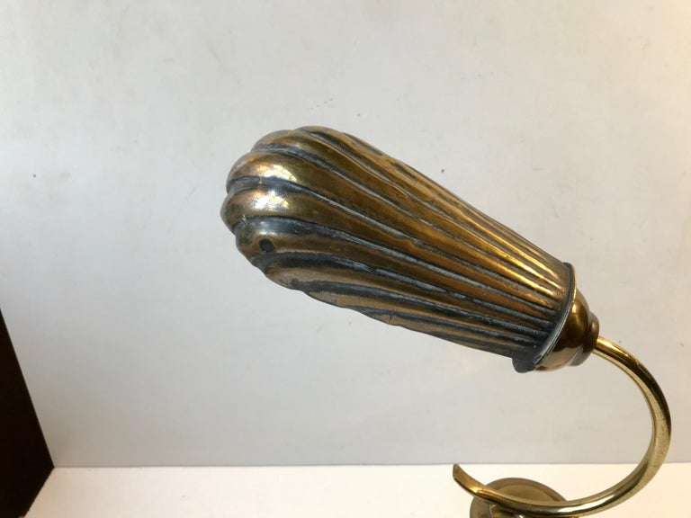 A very early table light with adjustable clam shell shade. Besides the centerpiece in stained oak everything is made from brass. It still has its original French bajonet socket but the cord and on/of switch has been replaced to accommodate modern