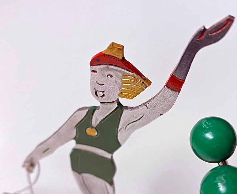 Very rare French Art Deco cocktail picks set, probably Sudre, circa 1930. White metal figural cocktail pick stand featuring a female skier with 6 pullout / pull-out cocktail picks, green plastic sphere terminals, as barware all on wooden base.
