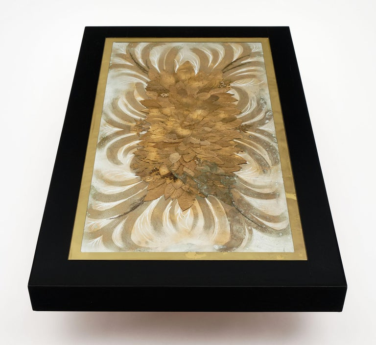 French Art Deco ebonized wood coffee table with glass top. It is made of ebonized oak and features gold leafed edges to the glass covering a gold leaf and natural decor decoration on aluminum. This piece of art is signed by N. Maillard.