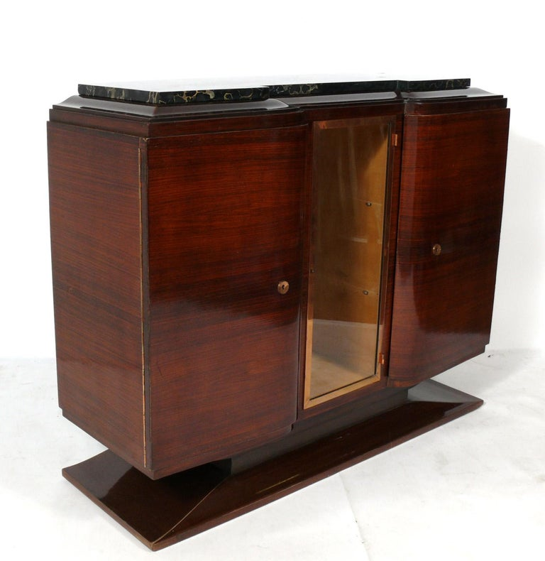 French Art Deco rosewood and marble-top credenza, France, circa 1930s. It is a versatile size and can be used as a credenza, bar, server, buffet, chest, or media cabinet. It offers a voluminous amount of storage, with the right and left doors
