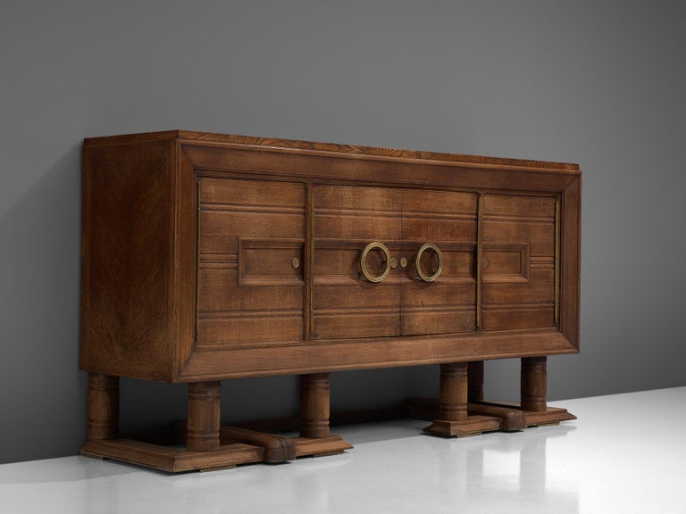 Credenza, oak and brass, France, 1940s.  Large Art Deco sideboard in solid oak with elegant brass details. A well designed piece that is crafted with beautiful elements, for instance geometric engraved front. The sideboard contains plenty of