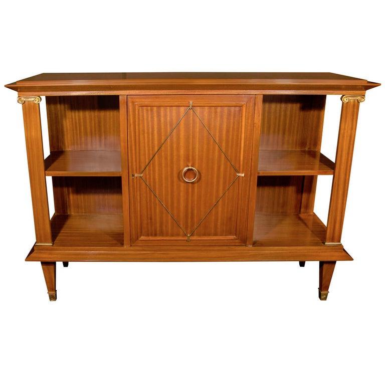 1940s French Art Deco sideboard cabinet and bookcase made of exotic ribbon striped Cuban mahogany wood. Neoclassical design features architectural elements with Directoire style accents. The sideboard has open display shelves on either side and a