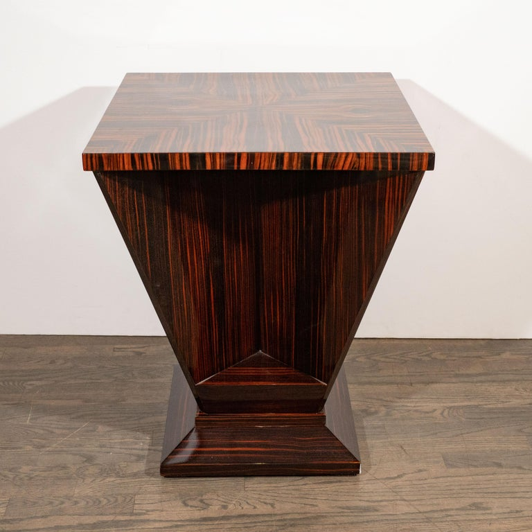 This dramatic occasional table was realized in France, circa 1930. It features a square top created from four triangular sections of bookmatched Macassar, which highlights the stunning natural grain of the wood, offering rich variegated tones and a