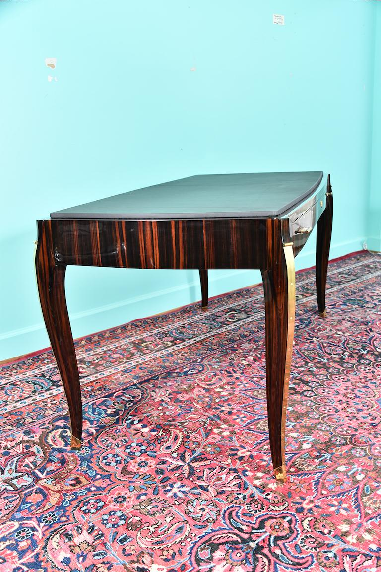 French Art Deco Desk in Macassar wood with leather top The desk is very comfortable with 3 storage drawers. 2 drawers have wide brass handles and a middle drawer has a key. The top of the desk is decorated with high quality dark brown leather. 4