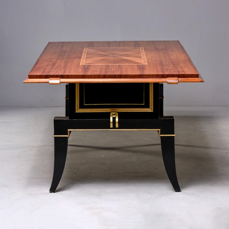 """French Art Deco dining table features a polished top with inlay details, beveled edge and contrasting black and giltwood base circa 1940s. Solidly constructed. Unknown maker.  Apron height 28""""."""