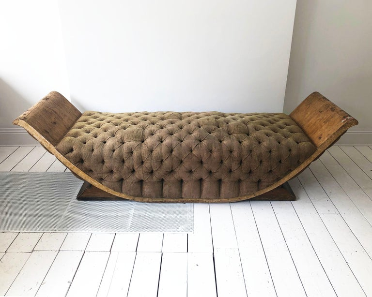 A unique 1930s Art Deco chaise lounge in the shape of gondola made out of burl walnut veneer and buttoned brown upholstery. The daybed talks history with its distressed look which shows its age and use over the decades but its very a comfortable