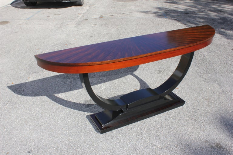 Long Classic French Art Deco exotic Macassar ebony ''Sunburst'' console tables, circa 1940s. Beautiful inlay design with ''Sunburst'' exotic Macassar ebony top, with ''U'' black lacquer center base, finish in both side, that rest on makes it ideal