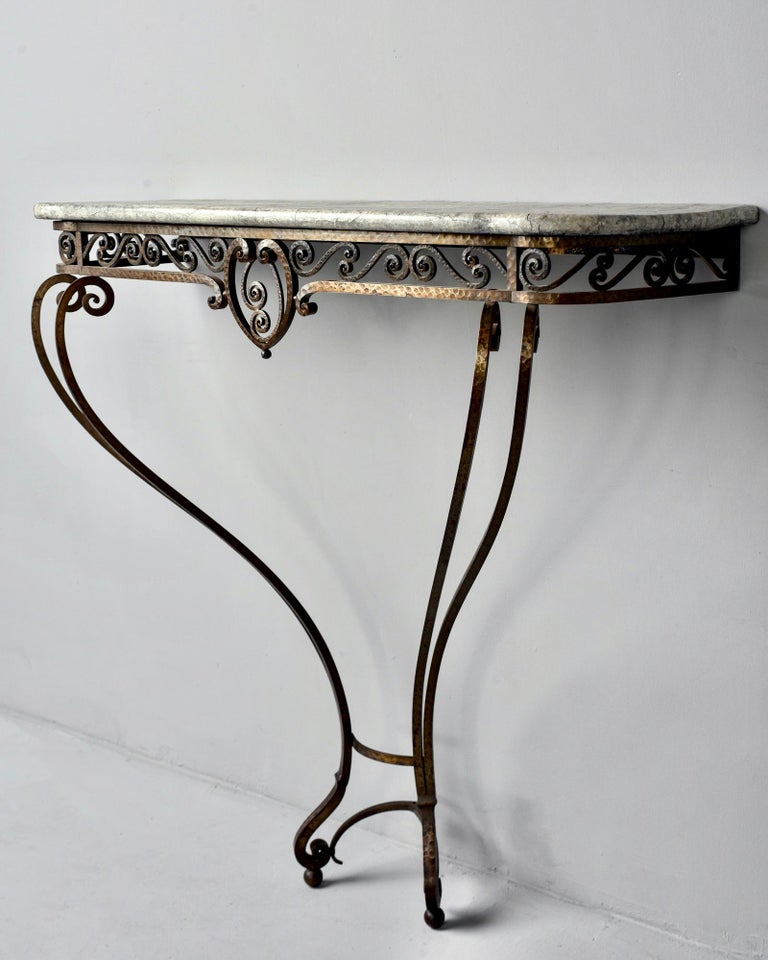 French Art Deco wall-mounted console features a hand forged, hammered iron base with lots of scroll work, circa 1930s. Top is wood with faux painted finish to mimic marble. Unknown maker.