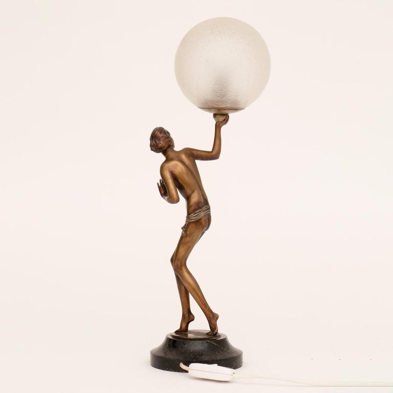 Semi nude Art Deco figure lamp holding aloft a crackle glaze illuminating globe, raise on a marble plinth. A figure by Lorenzl. Measures: H 57cm, W 19cm, D 13cm French, circa 1930.