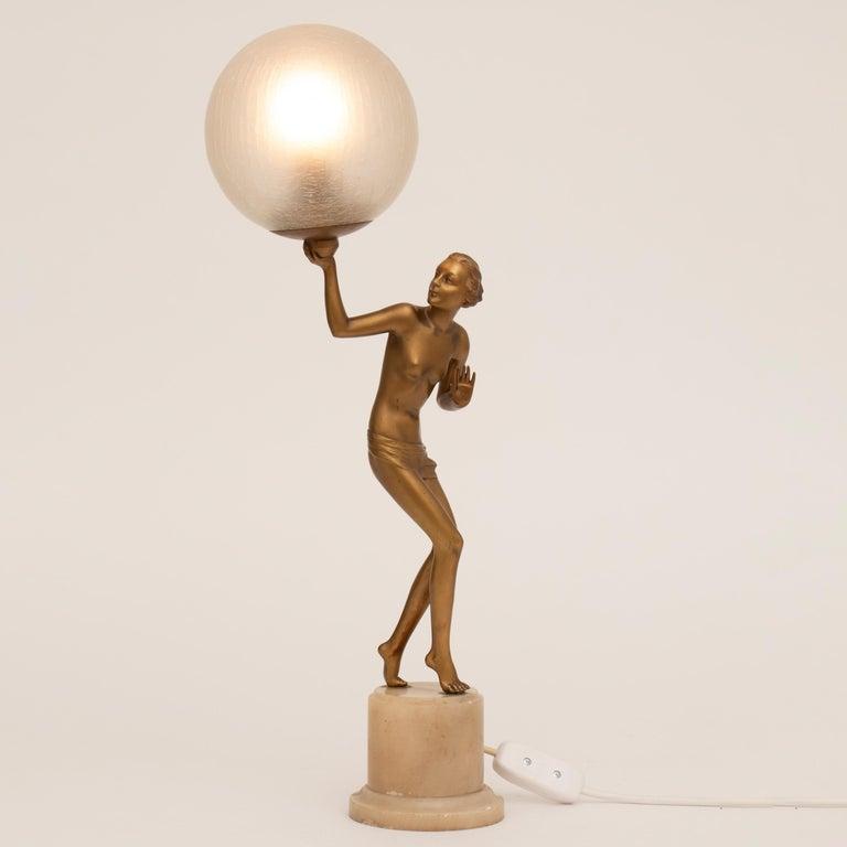 Semi nude Art Deco figure lamp holding aloft a crackle glaze illuminating globe, raise on a marble plinth. A figure by Lorenzl. Measures: H 60cm W 21cm D 24cm French circa 1930.