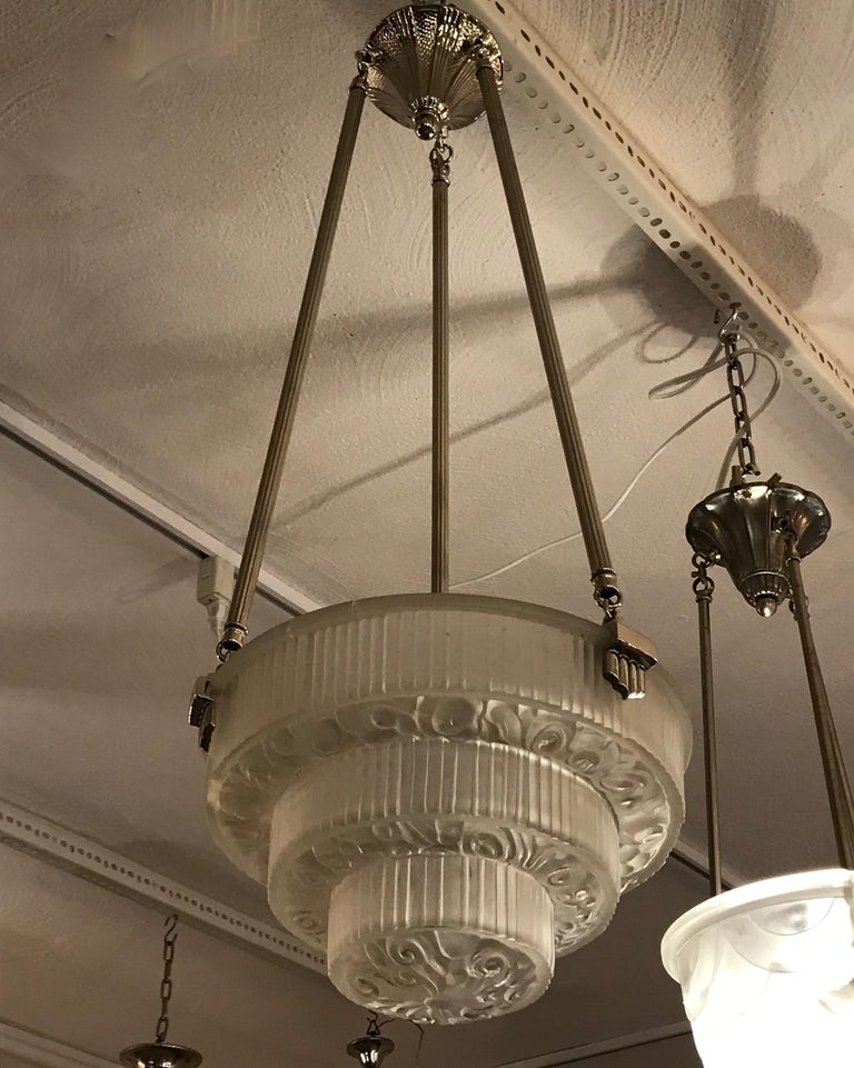 French Art Deco floral chandelier. With beautiful clear frosted glass bowl with three tiers of floral motif. Held by three nickel-plated metal rods and floral ceiling plate. Has been rewired for American use. One medium base socket with a max watt