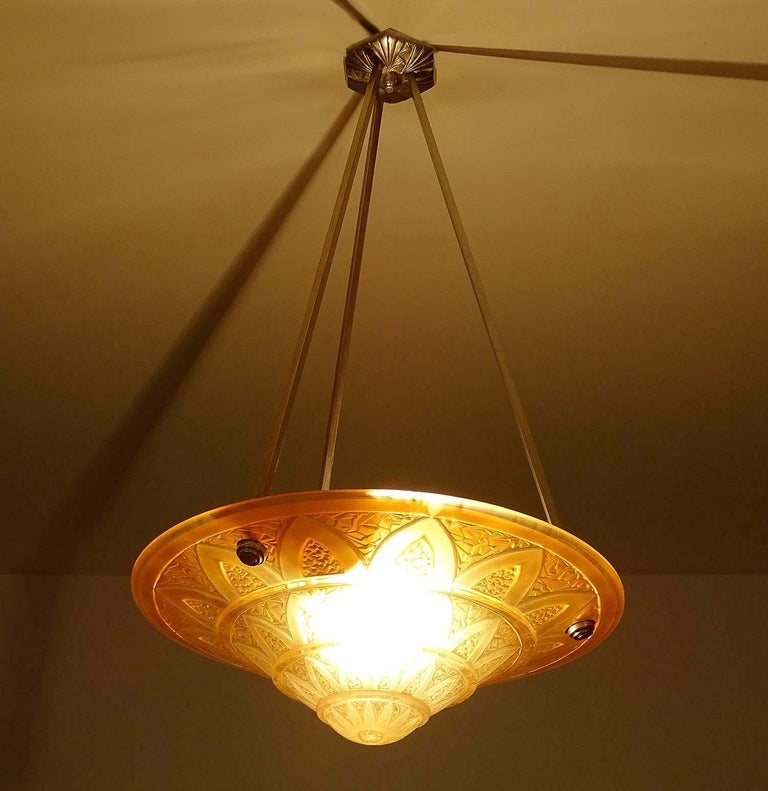 French Art Deco chandelier with molded glass shade showing geometric patterns inspired by ancient Egypt papyrus columns found in the Karnak temple, thick relief . Suspended on nickel plated bronze and brass fixture. Dimensions: H 25.6 in. x Dm 13.78