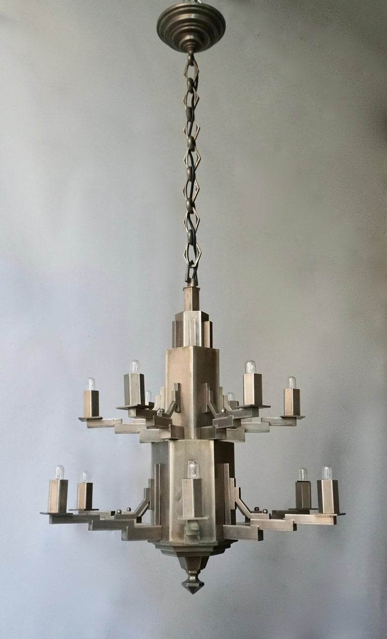 French Art Deco twelve-light chandelier with a two-tiered geometric base.  The light requires twelve single E14 screw fit lightbulbs (60Watt max.) LED compatible.  Measures: Diameter 56 cm. Height fixture 65 cm. Total height including chain