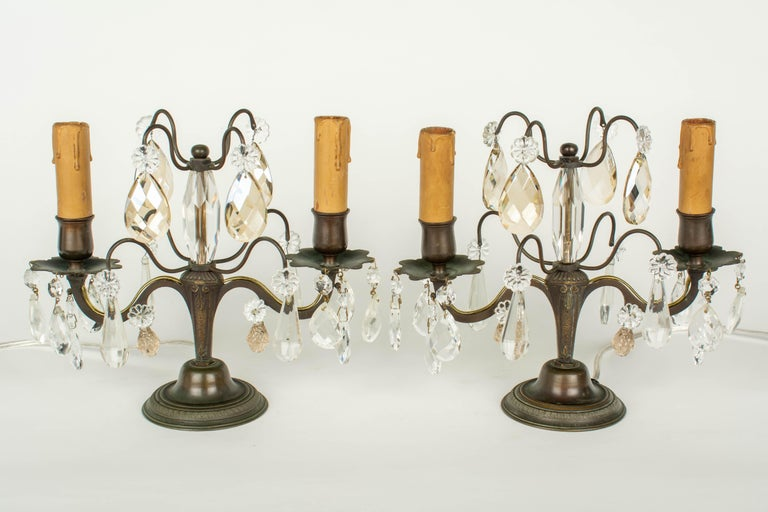 A pair of French two-light girandoles, or tabletop chandeliers. Brass frame with beautiful dark bronze and verdigris patina. Faceted crystal column, variety of prisms, as found, some clear and some champagne color, accented with rosettes, secured