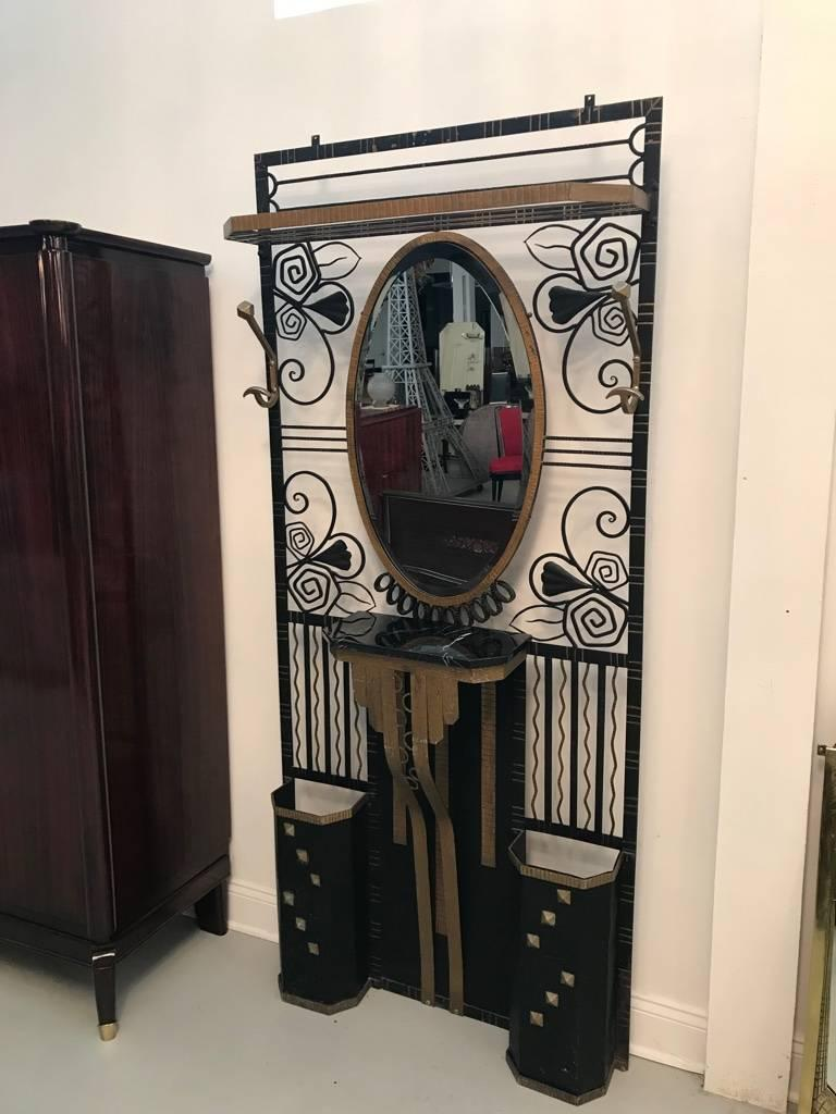 French Art Deco Edgar Brandt style hall tree with two umbrella stands. Having gilt and black ironwork accents. Beautiful marble shelf below a central oval beveled mirror. Two coat hangers and upper shelf for hats. The hall tree has geometric and