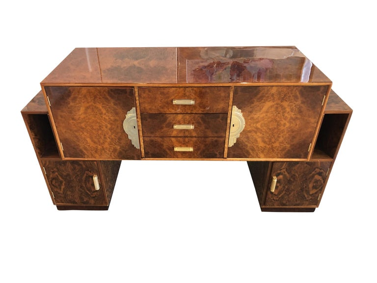 An exceptional French Art Deco sideboard cabinet crafted from burl with a lacquered finish and walnut veneer, circa 1930s. The wood has a warm honey-brown tone, while brass pulls, hinges, and trims add to the golden sheen. Its alluring grain pattern