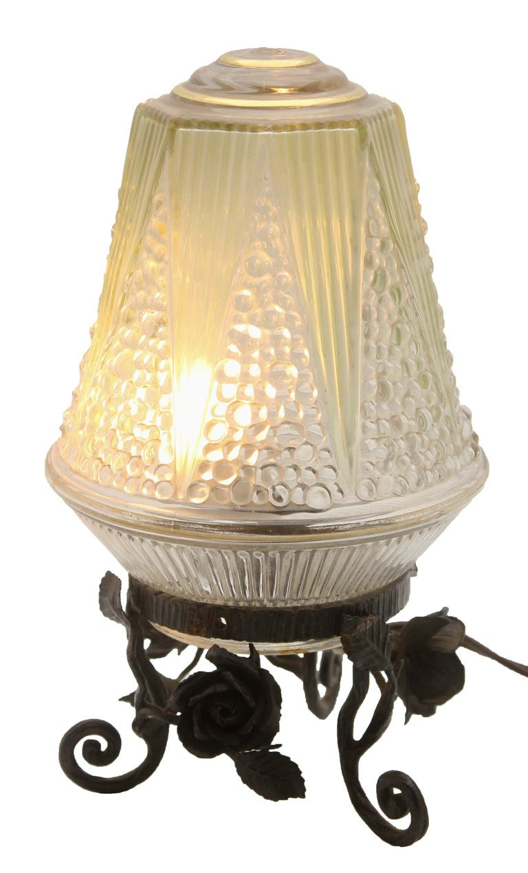 1933, Nancy, France A wonderful of French Art Deco lamp. The stand are handmade in wrought iron with black finish patina and hammered with floral pattern. The metalwork is of excellent quality. They are crowned with colored shade  In excellent