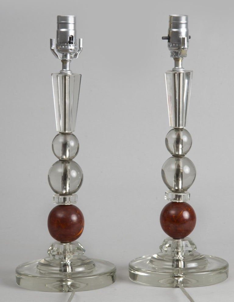 French pair of Art Deco lamps, circa 1920. Stacked above the round glass base are three spherical glass orb shapes, the bottom one being a dark amber color, atop those is a three and one-half inch tapered hexagonal shape.