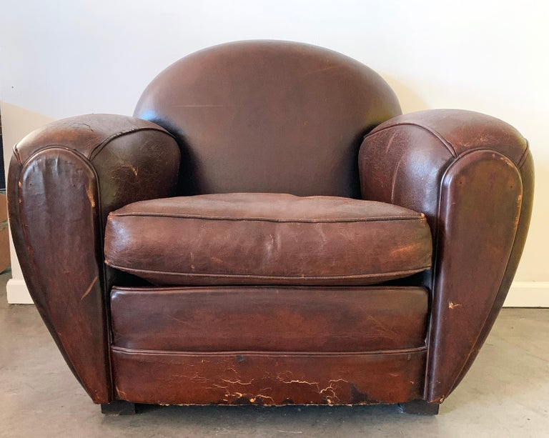 An absolutely round Art Deco leather club chair. This leather club chairs were purchased in the 1980s in Paris at the Les Puces de Saint-Ouen. The chair was re-dyed about 4 years ago and is in stunningly distressed condition with a wonderful patina