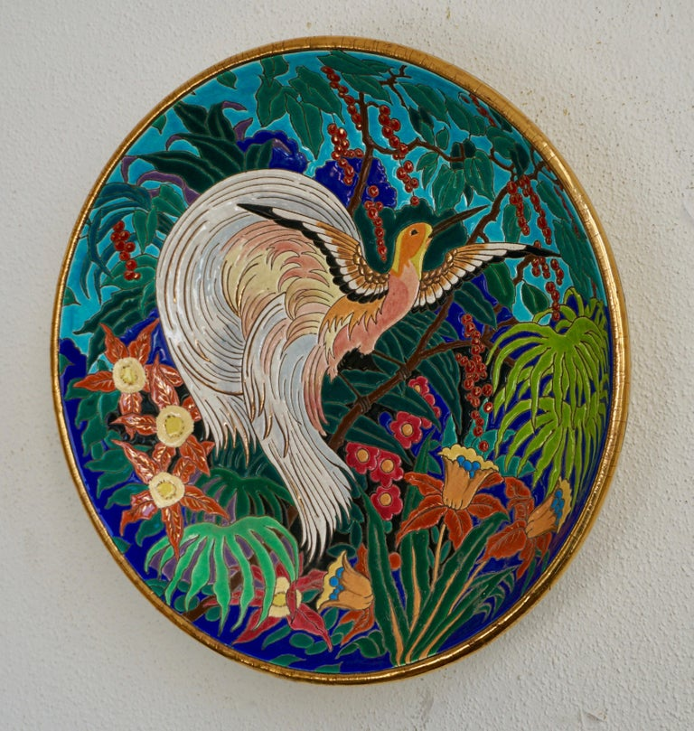 Wonderful large decorative French deep wall charger by Maurice Paul Chevallier for Fai¨ences de Longwy de Luneville. Decorated in a crackle glaze of vibrant colors and gilt and enameled with a bird surrounded by colorful foliage. Craquelle white