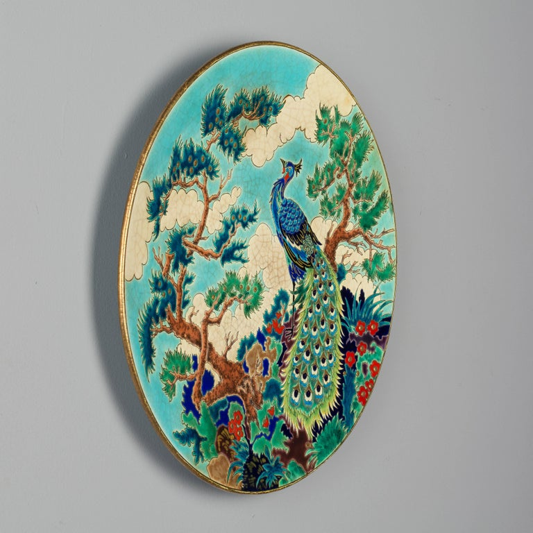A rare large decorative French deep wall charger by Maurice Paul Chevallier for Fai¨ences de Longwy de Luneville. Decorated in a crackle glaze of vibrant colors and gilt and enamelled with a peacock surrounded by colorful foliage. Craquelle white