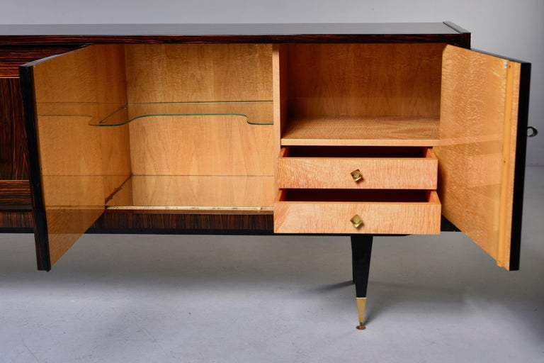 French Art Deco buffet or credenza in Macassar, circa 1940s. Cabinet front features elaborate geometric marquetry. Locking cabinets on each end with drawers top on one side with open storage above. The middle compartment features a glass shelf next