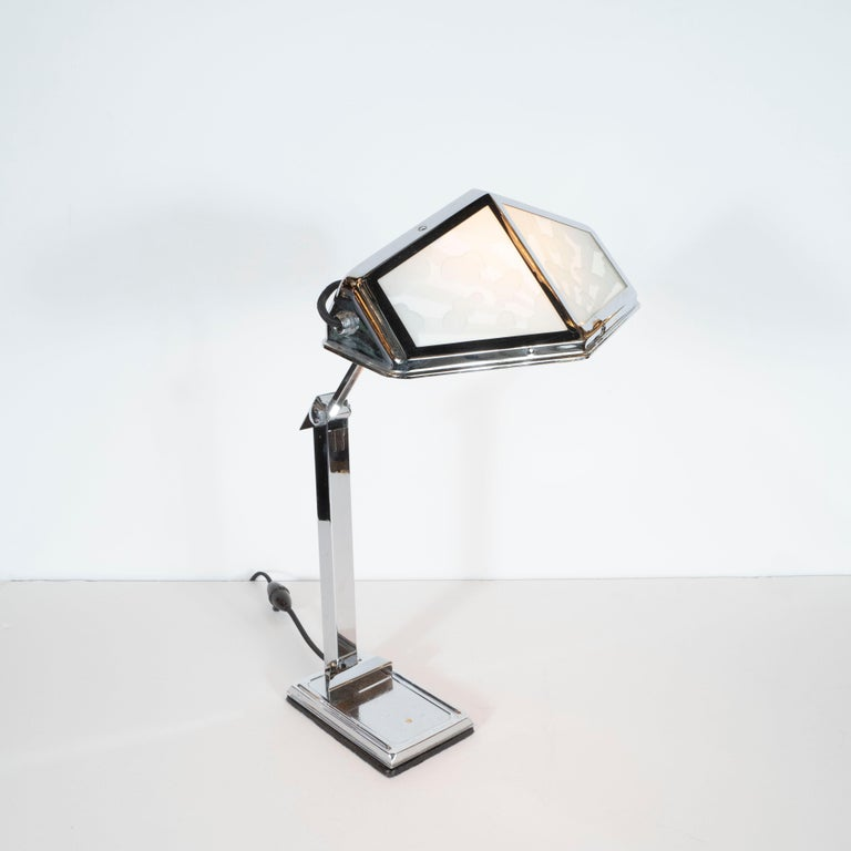 This stunning Art Deco Machine Age table lamp was realized in France, circa 1935. It features a shade 12 sided polygonal nickel frame that holds two pairs of glass shades in frosted glass (of two varying levels of opacity) on each side. Each