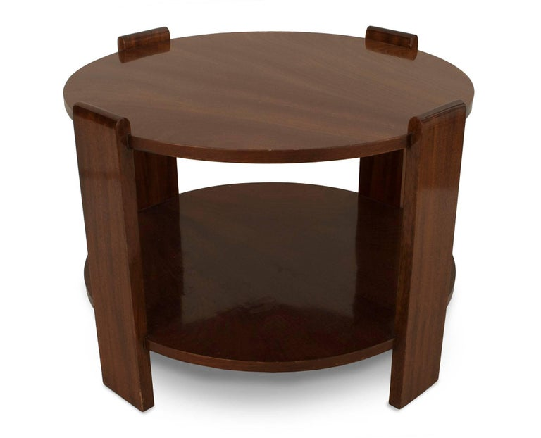 French Art Deco mahogany round coffee table with a shelf and supported by four round top side supports.