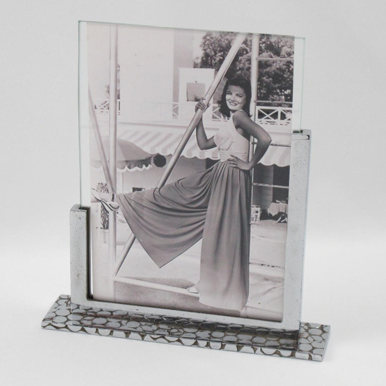 Lovely French Art Deco chrome picture photo frame. Modernist geometric shape with thick chromed metal plinth and straight holders. Plinth is all carved and textured with geometric design. The frame is complete with its two original glass sheets to