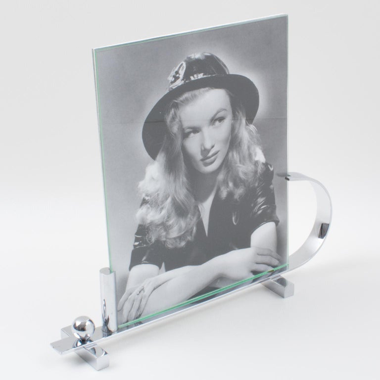 Elegant French Art Deco chrome picture photo frame. Modernist geometric shape with chromed metal feet and narrow plinth with asymmetric holders. The frame is complete with its two original glass sheets to enclose the