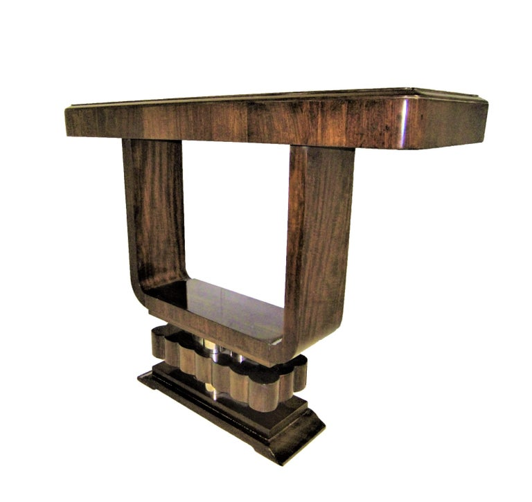 A fabulous original French Modern petite console of open cube form, raised on stepped and fluted pediment base. The negative area created in the center serves as a viewfinder which focuses our sight on the clean lines and simplicity of the form thus