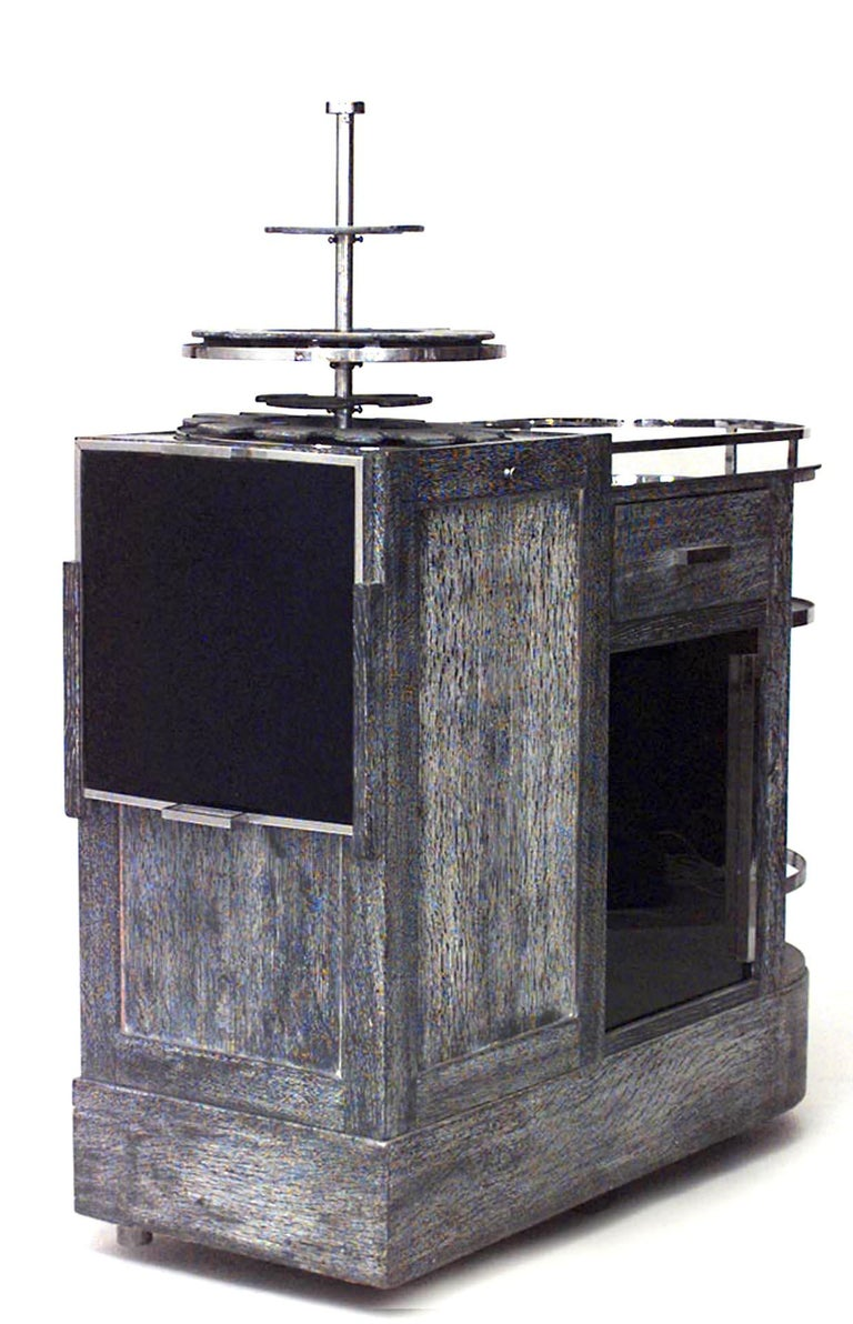 French Art Deco bar or tea wagon composed of bleached or pickled oak and featuring chrome trim, a black glass door, a drawer, and a serving section with a serving tray and tiered stand.