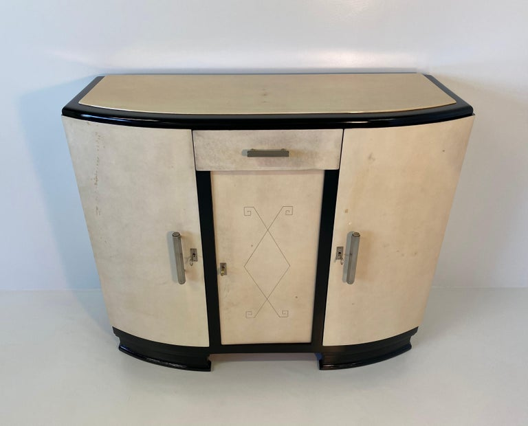 This fine and elegant Art Deco sideboard was made in France in the 1930s. It is completely covered in parchment and It has the base and profiles in black lacquered wood. The central decoration is engraved on the parchment and gives an unique touch