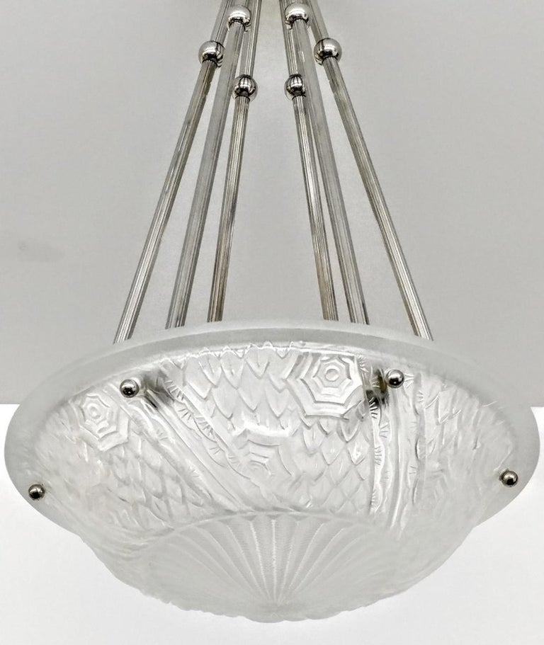 "A French Art Deco pendant chandelier by the French artist ""Schneider"". Clear frosted molded glass shades with intricate flowers and geometric polished motif details held by six ribbed rods with a dash of decorative balls extending from a matching"