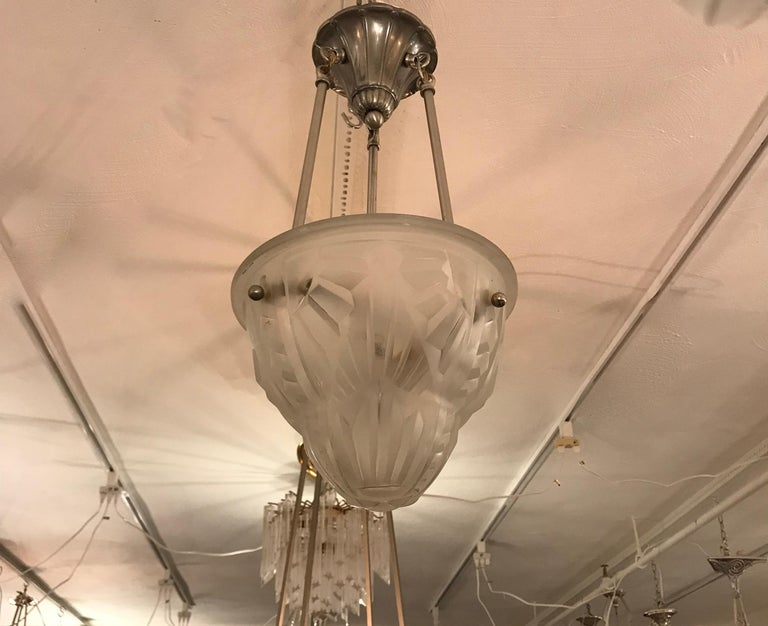 French Art Deco pendant chandelier by the French artist Degue. Clear frosted glass shade with geometric motif. Held by three nickel rods and ceiling plate. Has been rewired for American use with three candelabra sockets. Each socket has a max of 60