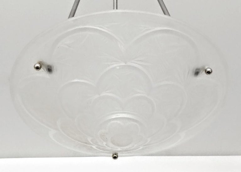 """A French Art Deco pendant chandelier by the French artist """"Hanots"""". The clear frosted molded glass shades is with intricate geometric polished motif details (marked Hanots). Held by three smooth rods with decoration weld by a matching canopy. The"""