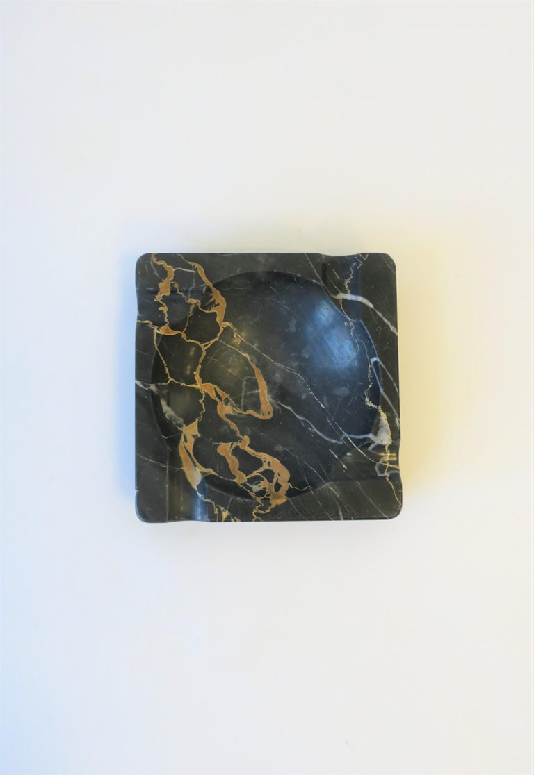 A beautiful and substantial French Art Deco period black marble ashtray or vide-poche (catch-all.) Ashtray can accommodate cigarettes or cigars. Piece is black marble, with tan and white veining, aka as 'Portoro Marble'. As show in images, piece can