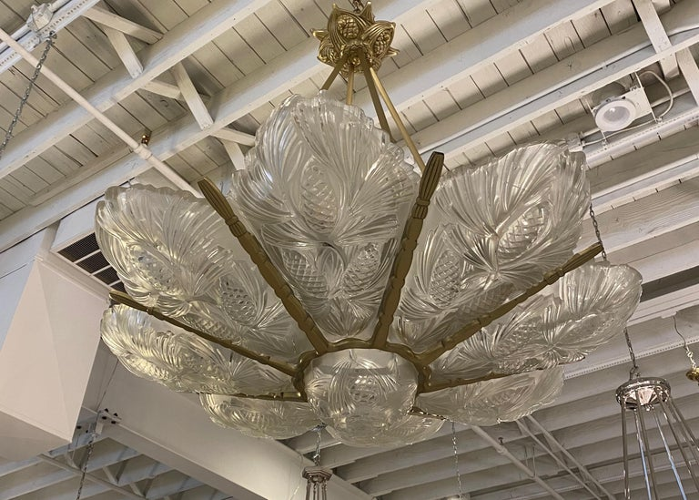 French Art Deco chandelier signed by famous artist Sabino. Having Eight outer panels and center bowl with pine cone motifs. The glass rest in a brass design frame. The pine cone motif continues on the ceiling plate. The chandelier has been fully