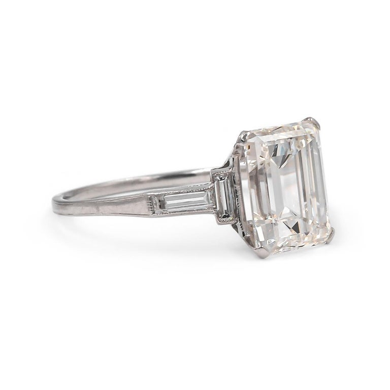 Clean lines embody this classic Art Deco engagement ring of French Origin. Composed of Platinum & featuring a spectacular GIA certified 3.07 Carat Emerald Cut Diamond, I color and VIS1 clarity. Flanked by 4 Straight Baguette Cut Diamonds weighing