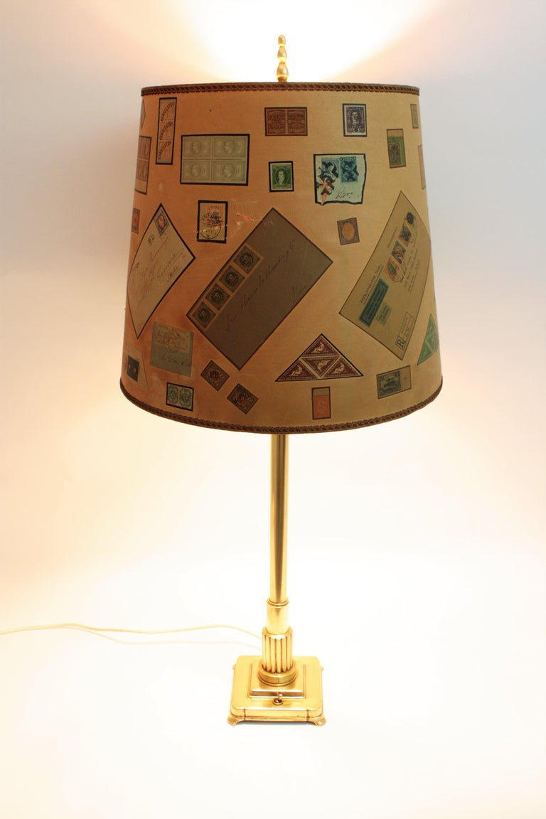 Stylish Art Deco two lights polished brass table lamp. France, 1930s. The column body of this lamp holds its original antique funny paper shade with stamps and letters. The brass has been polished and varnished. Sold with shade. Measures without